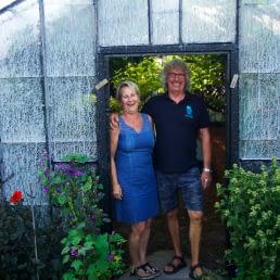 Hilde en Arnold Janssen poseren in de deuropening van een historische glazen kas van hun druivenkwekerij Nieuw Tuinzight in het Westland