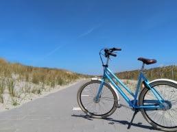 Blauwe damesfiets met witte spatborden en een zwart zadel op een leeg fietspad in de duinen in het Westland met een zomerse blauwe lucht in de achtergrond