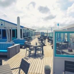 foto van het blauw witte terras van strandtent Moments Beach op het strand in het Westland