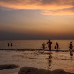 families die op het strand van het Westland aan het zwemmen zijn in zee nadat de zon is ondergegaan aan de kust
