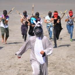 deelnemers aan de groepsactiviteit 'Shoot Out' van Wato Events rennen met pijl en boog aan achter iemand die verkleed is in een konijnenpak op het strand in het Westland