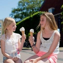 Twee jonge meisjes die op een bankje zitten op het Marktplein in Naaldwijk en een ijsje eten op een warme zomerse dag