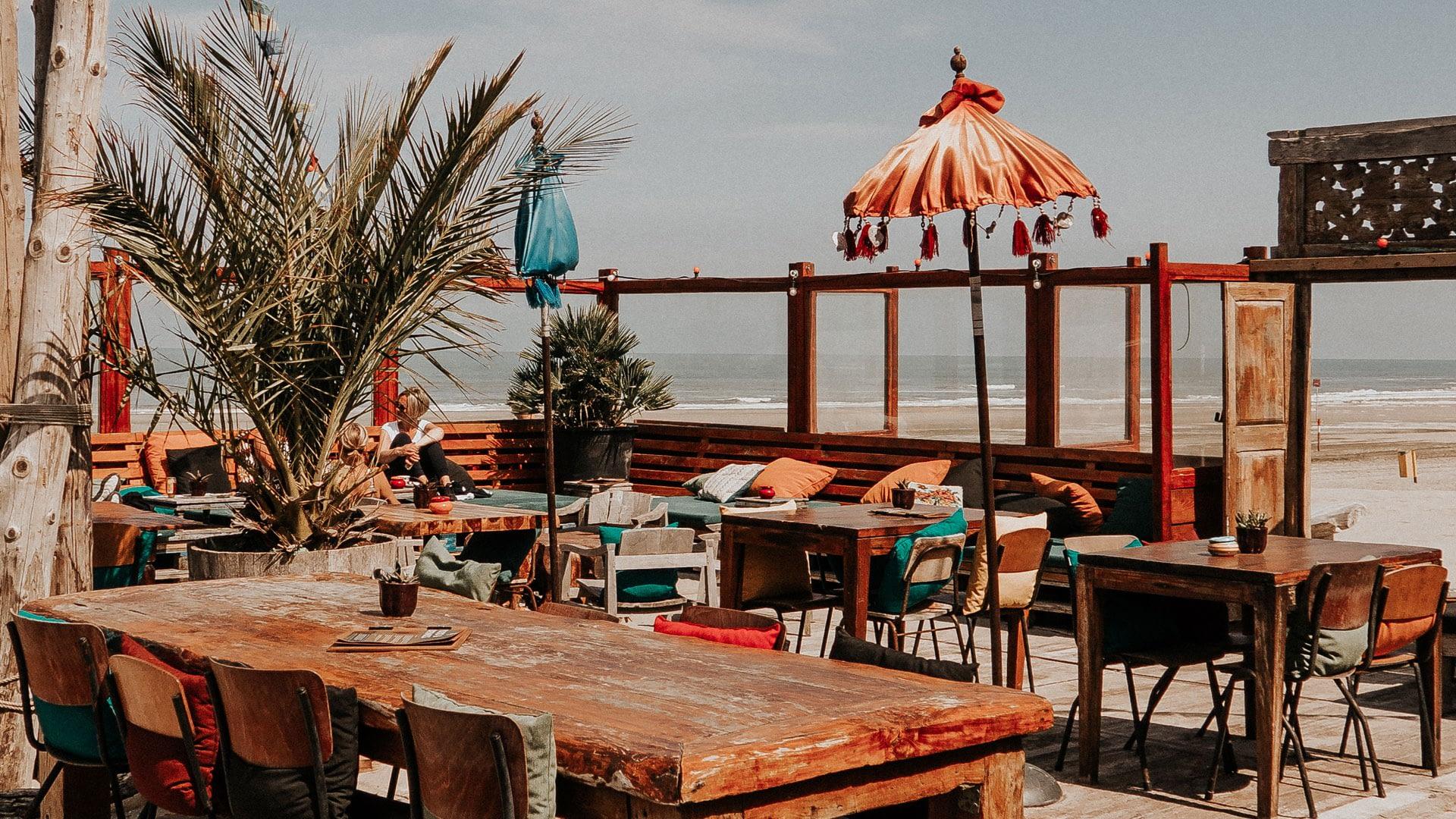 Terras van strandtent Elements Beach met balinese parasol , teakhouten terrastafel en de zee in de achtergrond aan het Westlandse strand