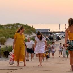 Strandopgang Beukel met strandbezoekers in zomerse kleding die van en naar het strand wandelen in warm avondlicht in het Westland
