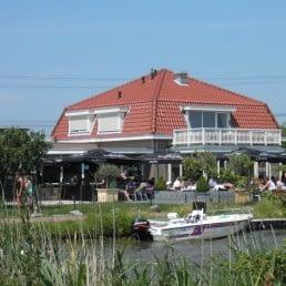 uitzicht over het water op het pand en terras van eetcafé de Bonte Haas met bootjes voor de deur in het Westland