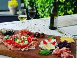 houten plank met Italiaanse anti-pasta gerechten op een witte houten tafel met twee glazen wijn en een fles wijn in de achtergrond bij Poveretti in het Westland