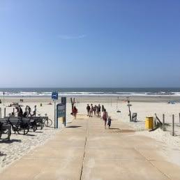 strandopgang Vlugtenburg naar het strand in het westland op een zonnige zomerse dag met mensen die met strandspullen richting het strand lopen
