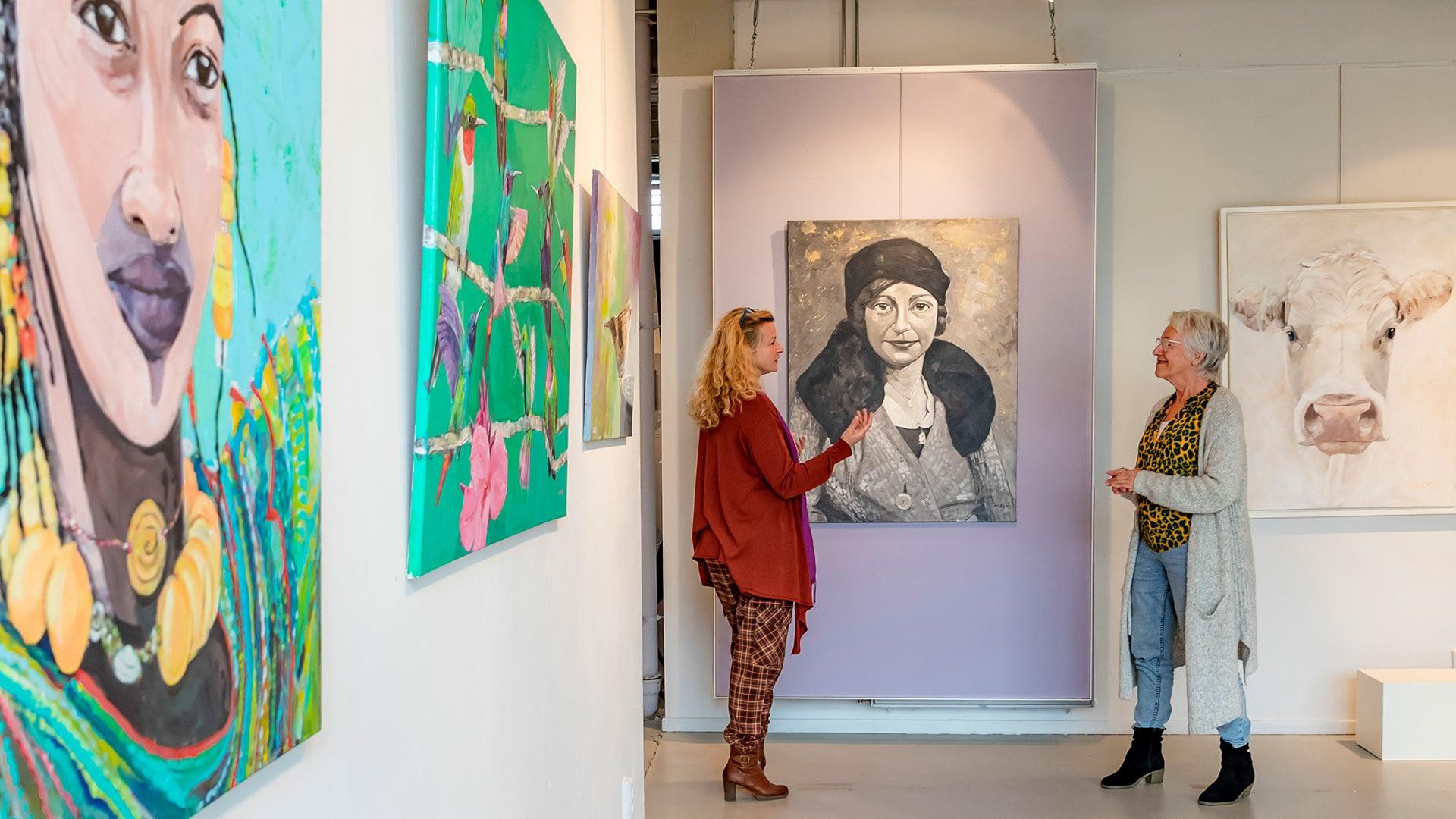 foto van Rolf van Koppen met twee dames staan te praten bij galerie Kunsthuis18 in het Westland met aan de muur grote schilderijen