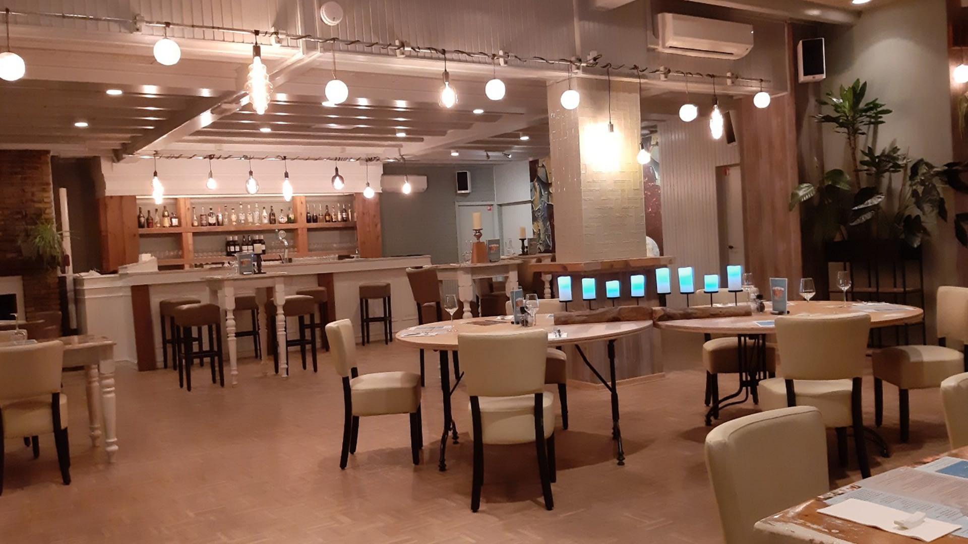 restaurantgedeelte met witte tafels en stoelen bij Eindeloos uit eten in het Westland