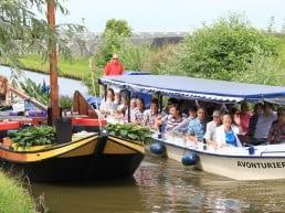 Rondvaartboot van Rondvaart Westland vaart langs een varende oude Westlander die wordt opgebouwd met bloemen, groenten en planten voor het Varend Corso in het Westland
