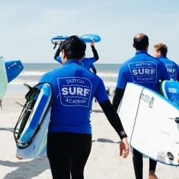 grosp sufers met zwarte wetsuits en blauwe t-shirt lopen op het strand met surfboards onder de arm richting de zee in het Westland