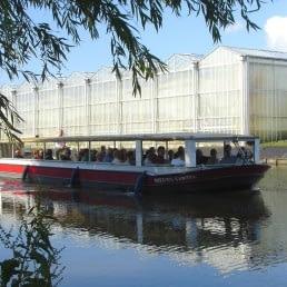 Rondvaartboot van Rondvaartbedrijf De Gantel vaart met gasten aan boord door het Westland met op de achtergrond glazen kassen in de zon