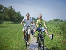 Lachende vader en zoon op een huurfiets in een groen landschap in het Westland