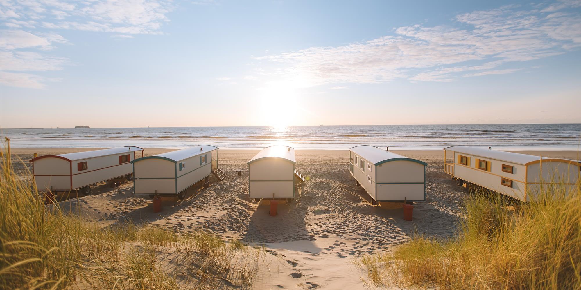 5 pipowagens op het strand van het Westland met duinen op de voorgrond en de zee in de achtergrond