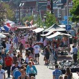 drukke straat in De Lier tijdens een feestelijke dag met kraampjes langs de weg en veel wandelende mensen op straat in De Lier in het Westland