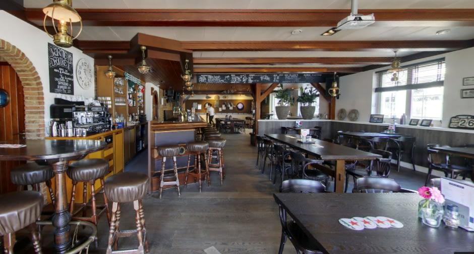 interieur van café De Jachthaven met bruine tafels en stoelen en houten balken aan het plafond in het Westland