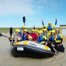 foto van een groep enthousiaste mensen die gaan raften in wetsuits en met gele helmen en roeispanen in een rubberen boot op het strand van Ter Heijde in het Westland