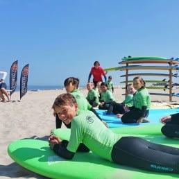 Jonge kinderen die met groen-zwarte wetsuits aan liggen te wachten op hun surfboard tijdens een surfles van Dreams Surfschool in het Westland