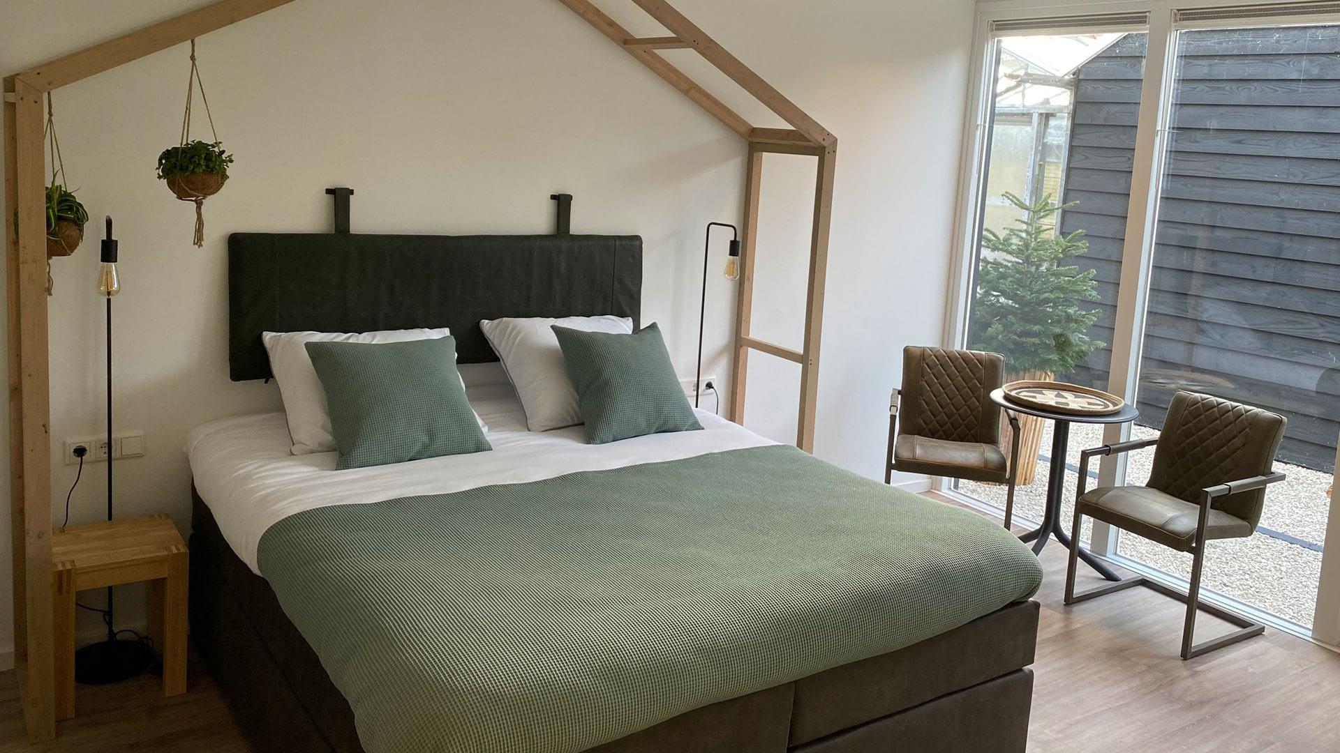 Tweepersoons bed in een B&B met groen/grijze dekbed en een houten frame van een kas boven het bed in het Westland