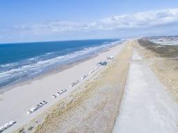 Luchtfoto van een leeg strand in het Westland met links de zee en rechts de duinen