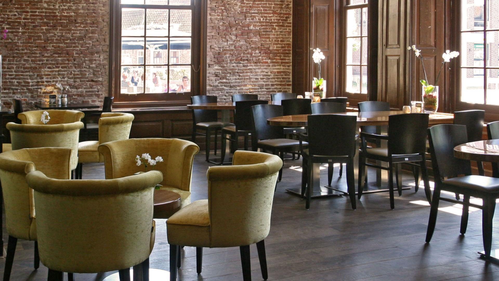 Zaal bij Restaurant Bij5 met groene ronde zitjes en donkere tafels met houten stoelen