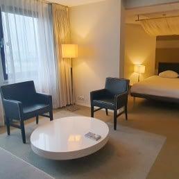ruime hotelkamer in Fletcher Hotel Restaurant Carlton in het Westland met een hemelbed en een zithoek met losse stoelen en een grijze bank