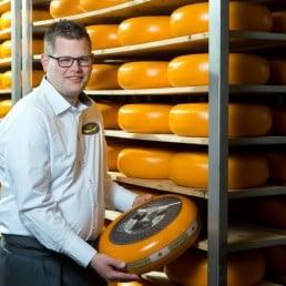 kaasmeester Ricard voor een schap vol met goudgele kazen in het Westland