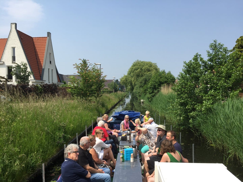 Rondvaartboot van Rondvaart Westland vaart een geheime route met groen riet en bomen langs de kant in het Westland