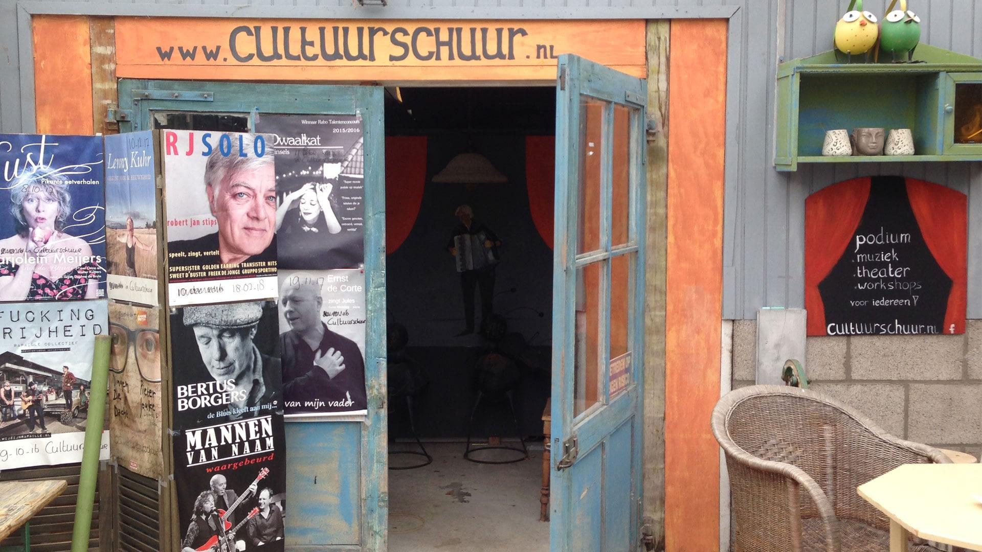 Houten deur beplakt met poster van artiesten is de toegang tot de Cultuurschuur in het Westland