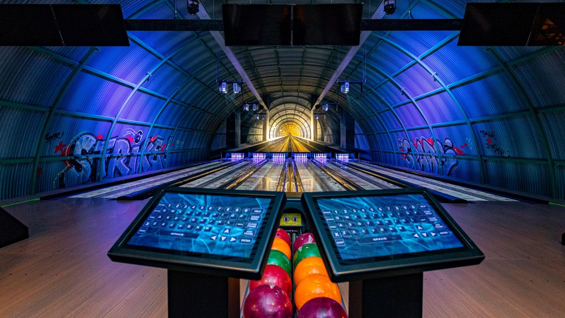 glow in the dark bowlingbaan in een metalen loods met fel gekleurde bowlingballen in entertainment center The City in het Westland