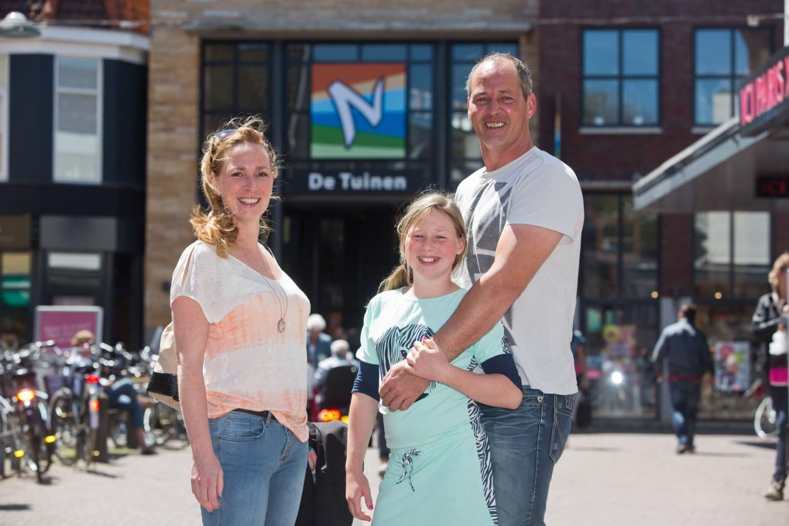 gezin met jonge dochter poseren voor de ingang van Winkeldentrum de Tuinen in Naaldwijk in het Westland