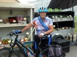 Marja van der Ende poseert met haar fiets voor een stalletje met streekproducten uit het Westland