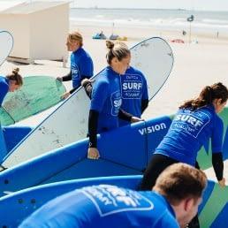groep cursisten op het strand tijdens een les golfsurfen van Dutch Surf Academy in het Westland
