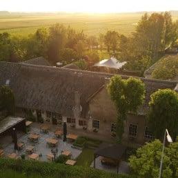 luchtfoto van de boerderij van Brasserie Oostgaag met het terras aan de voorzijde en de achterzijde van het pand in Midden-Delfland