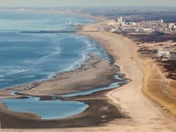 luchtfoto van de Zandmotor bij de kust van Monster met een leeg strand een binnenmeer