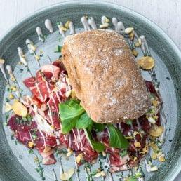 blauw-groen bord met daarop een broodje carpaccio bij strandtent Bondi Beach Club in Monster in het Westland