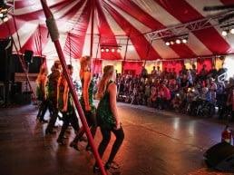 optreden van een groep jonge vrouwen in een rood-wit gestreepte circustent in het Westland