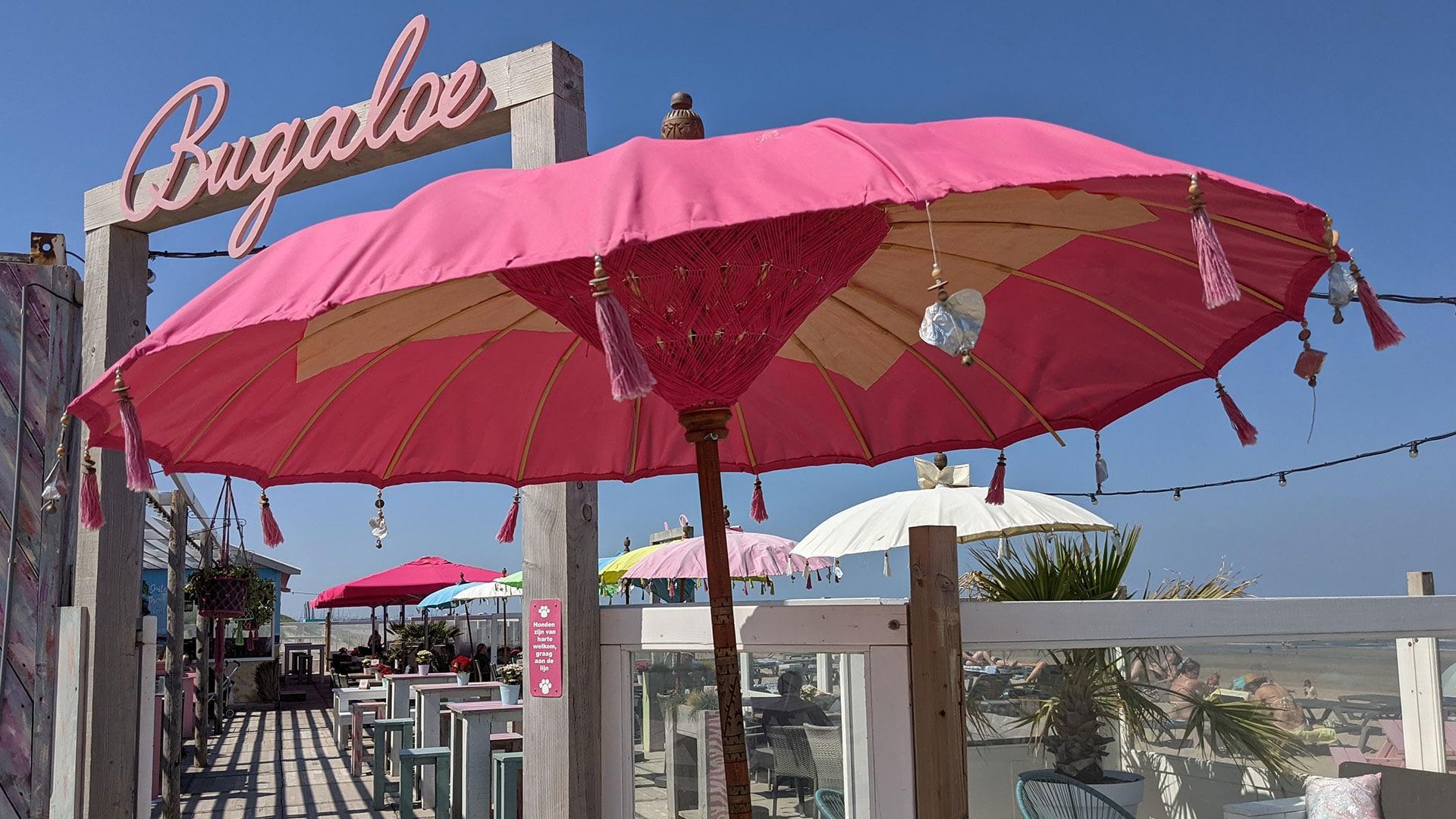 entree van strandtent Bugaloe Beach met houten poort met de naam van Bugaloe Beach in roze letters en een grote roze Balinese parasol in het Westland