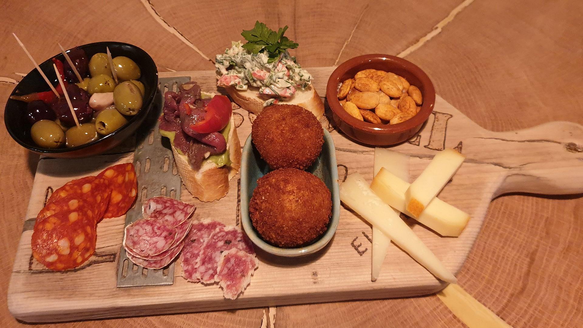 houten tapasplank bij Restaurant Eindeloos in het westland met olijven, kroketjes, kaas, salami, pittige worst en pinda's