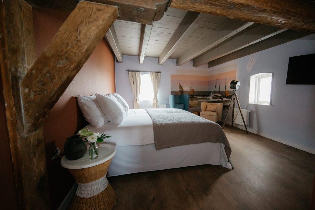 kamer van Boutique Hotel De Gravin in het Westland met bed, houten balken en muurschildering