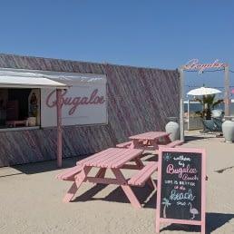 take away luik met roze hoiten zitbanken bij strandtent Bugaloe Beach in het Westland