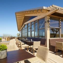 Hooggelegen terras van Restaurant The Coast in Monster met houten vloer, rieten stoelen en glazen gebouw met houten balken dak