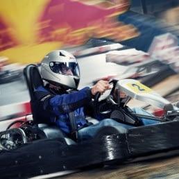 man rijdt op hoge snelheid in een kart van Van der Ende Racing Inn op de grootste indoor kartbaan van Europa in het Westland
