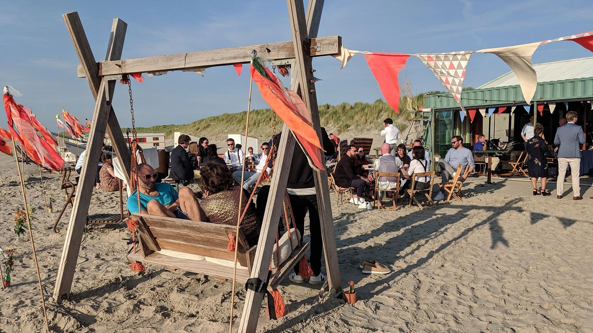houten schommel op het strand bij Strandtent De Pit inn het Westland op een zonnige dag met in de achtergrond mensen die genieten van een feestje aan het strand