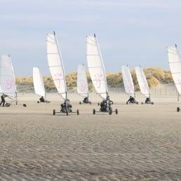 8 blokarts met witte zeielen van Wato Events rijden over een leeg strand in het Westland