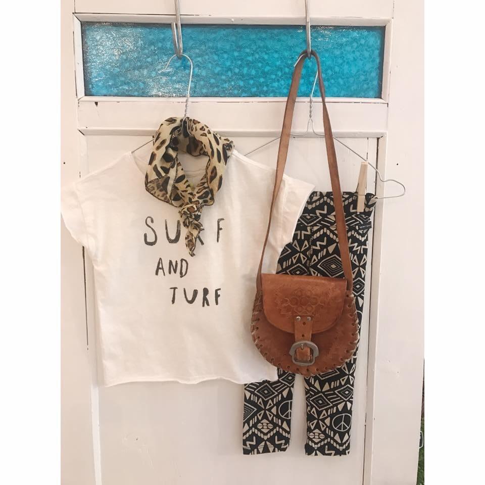 foto van een t-shirt, broek en handtas op een hangertje aan een deur tijdens een vintage markt bij Rumah conceptstore in het Westland