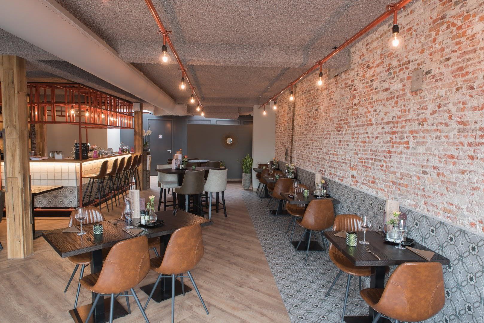 interieur van restaurant Het Galjoen in het Westland met vierknte tafels en lichtbruine lederen stoelen