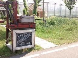 Houten stalletje langs de weg in het Westland met een zwart krijtbord waarop courgettes te koop staan met in de achtergrond glazen kassen in het Westland