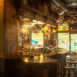 Interieur van bruine kroeg De Slimmerick in Naaldwijk met een bruine bar, barkrukken , zacht licht en hangende glazen boven de bar