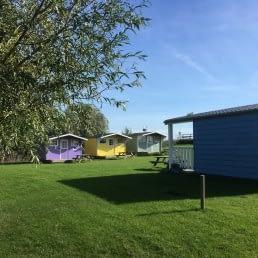 grasveld met 5 felgekleurde houten trekkershutten bij Minicamoing Zwetzone in het Westland